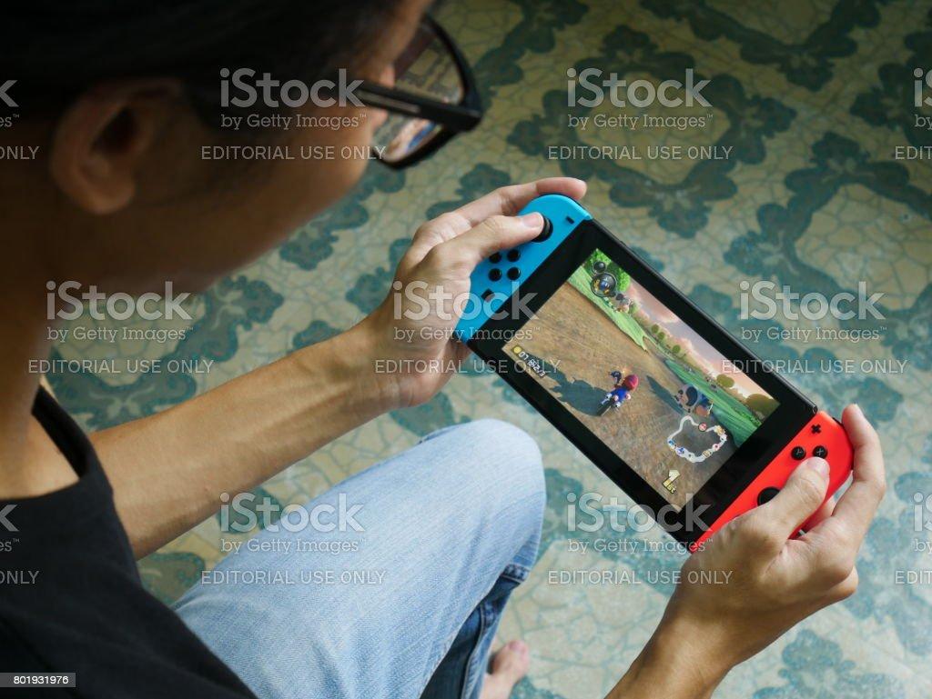 Bangkok, Thailand - June 25, 2017 : A man playing Mario Kart 8 Deluxe on Nintendo Switch. stock photo