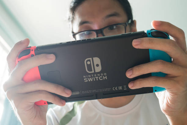 A man playing Nintendo Switch. Bangkok, Thailand - October 31, 2017 : A man playing Nintendo Switch. nintendo stock pictures, royalty-free photos & images