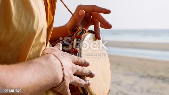 Man playing on a drum with his hands on the sandy beach, close up. Hands tapping a small drum outdoor