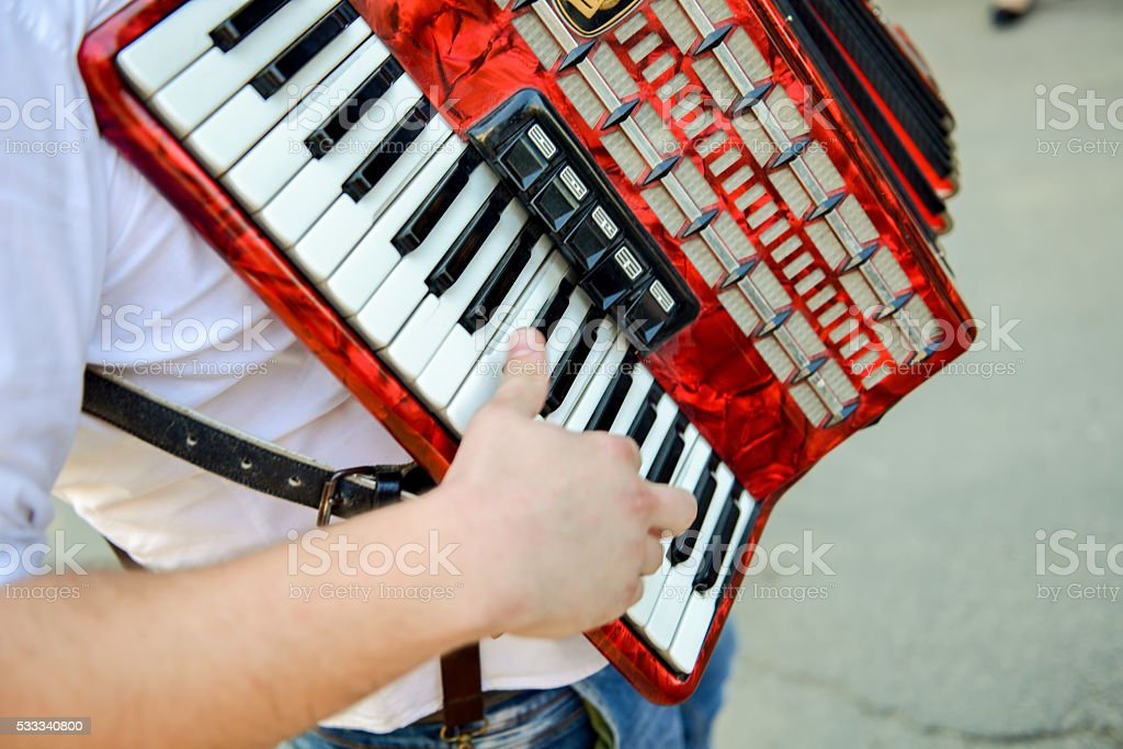 Man playing on a electronic accordion in natural light stock photo