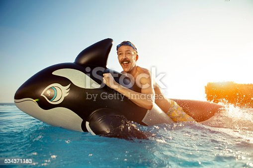 Man playing on a inflated whale. Generic produced inflatable, there already images accepted with this product.