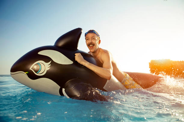 Man playing on a inflated whale stock photo