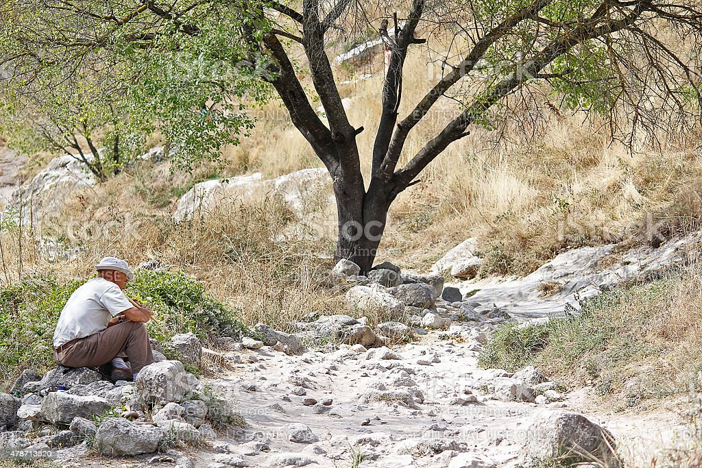 Man playing on a pipe sitting on the tourist trail stock photo