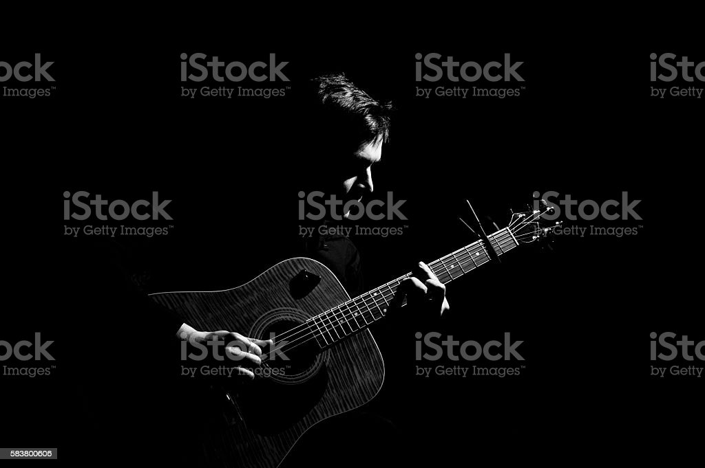 Man playing on acoustic guitar stock photo