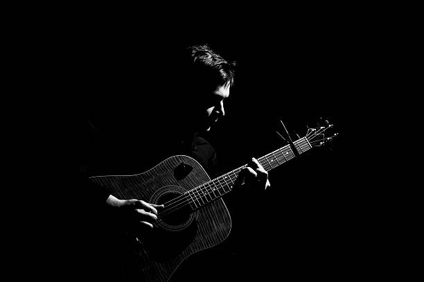 Man playing on acoustic guitar - foto de acervo