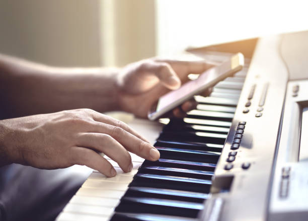 Man playing piano and using mobile phone. Person recording sound, reading notes from smartphone screen or writing lyrics for a song. stock photo