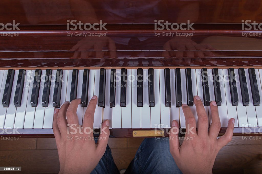 Man playing piano with both hands stock photo