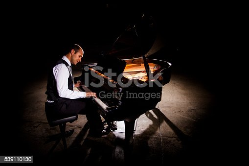 Attractive young man playing piano with dramatic lighting