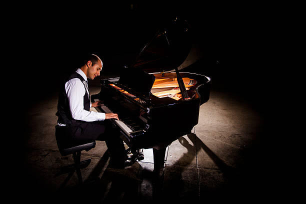 Man Playing Piano with Dramatic Lighting Attractive young man playing piano with dramatic lighting pianist stock pictures, royalty-free photos & images