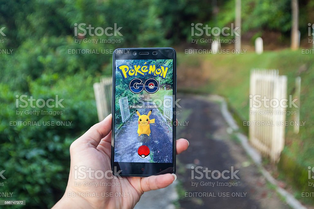 Man playing Pokemon Go with blur background stock photo