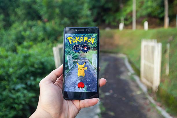 man playing pokemon go with blur background - pflanzen pokemon stock-fotos und bilder