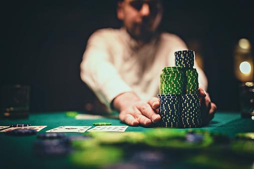 Man playing poker in dark room at night