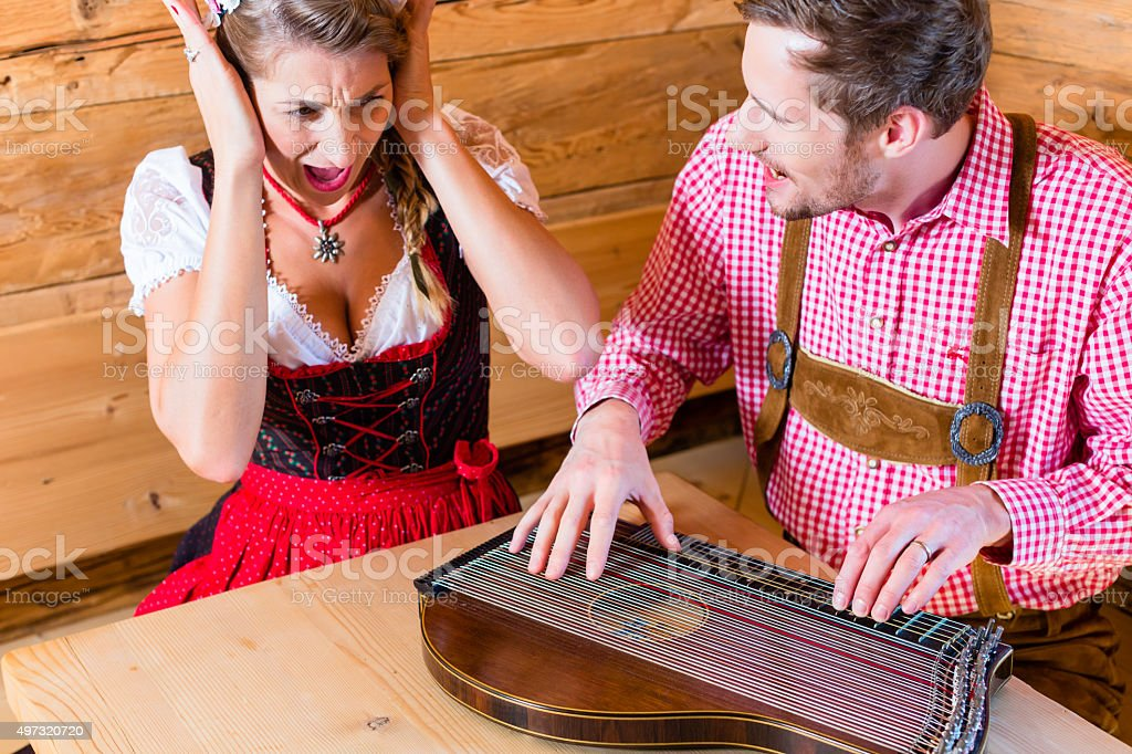 Man playing poorly on zither in mountain hut stock photo