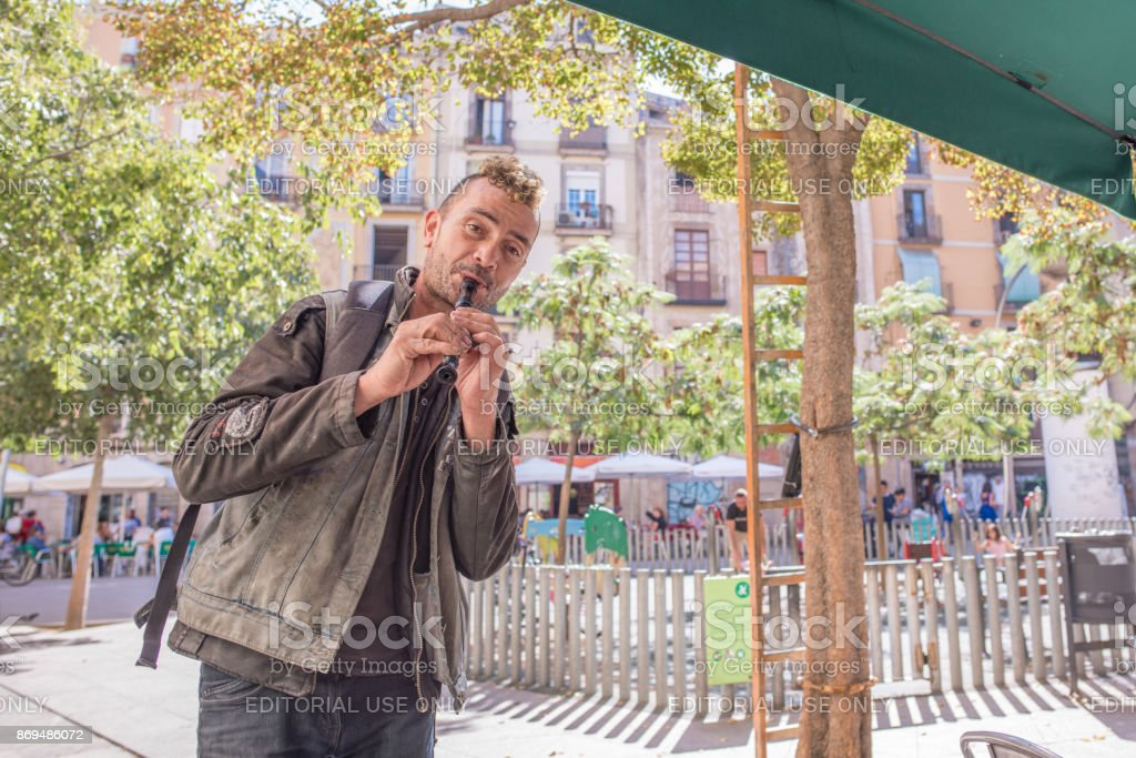 Man playing recorder for tips in George Orwell Plaza in Barcelona stock photo