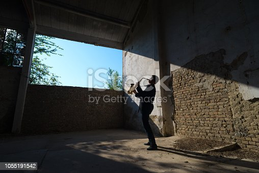 Man playing saxophone in an abandoned building on a sunny day.