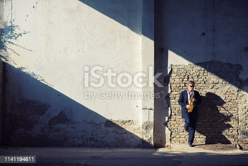 Young elegant man playing saxophone in an abandoned building.