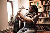 Mature man playing saxophone in studio, having fun.