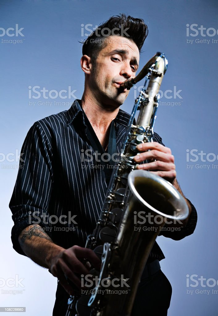 Man Playing Saxophone On Blue Background royalty-free stock photo