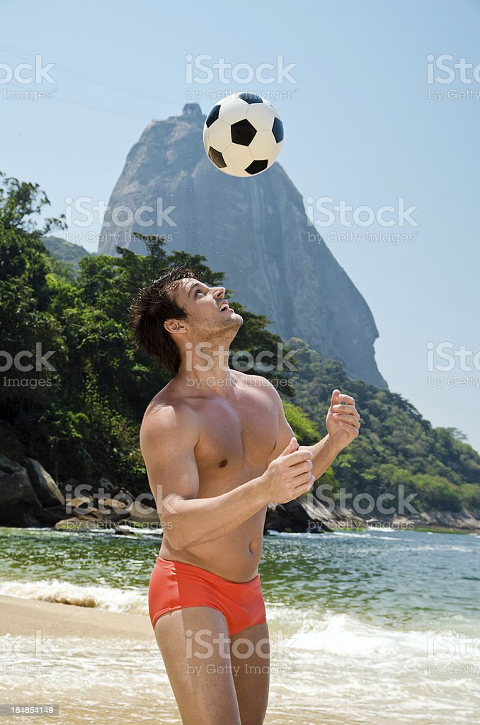 Man playing soccer on beach stock photo