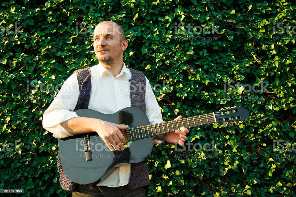 Man playing spanish guitar in green garden stock photo