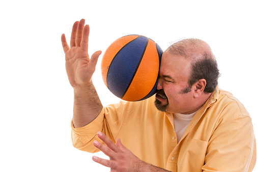 Man playing sport being hit by a basket ball