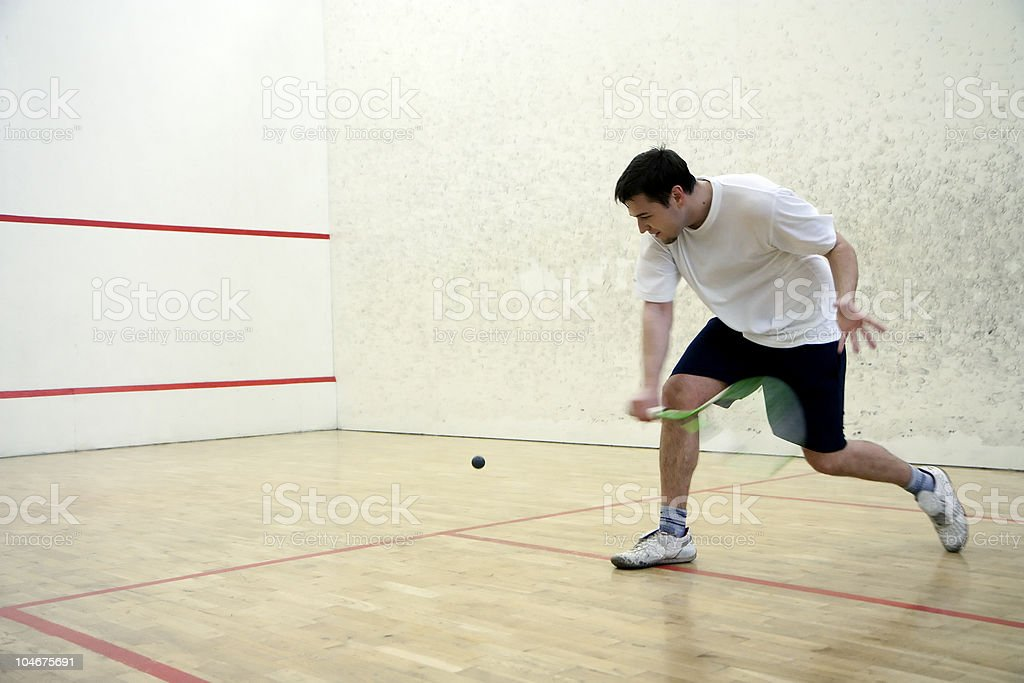Man playing squash alone with a green racket stock photo