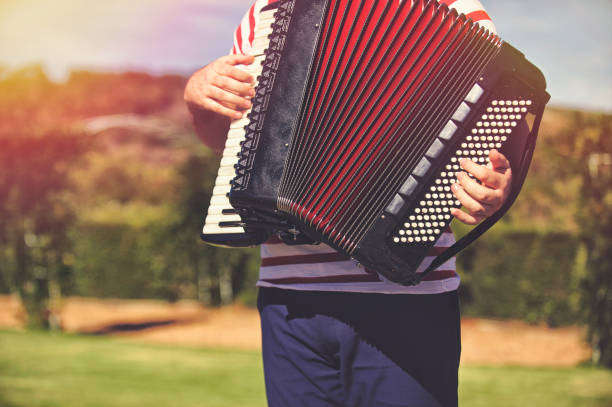man playing the accordion outdoors - accordion stock photos and pictures