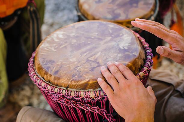 A man playing the djembe between his knees stock photo