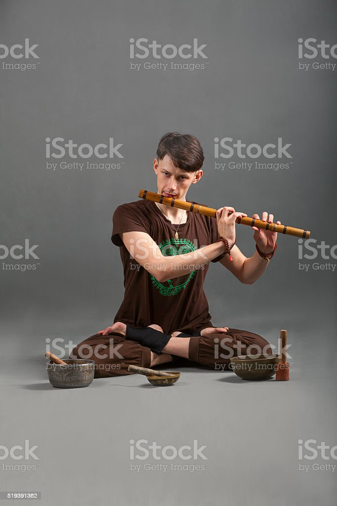 Man playing the flute, singing bowls and tools for meditation. stock photo