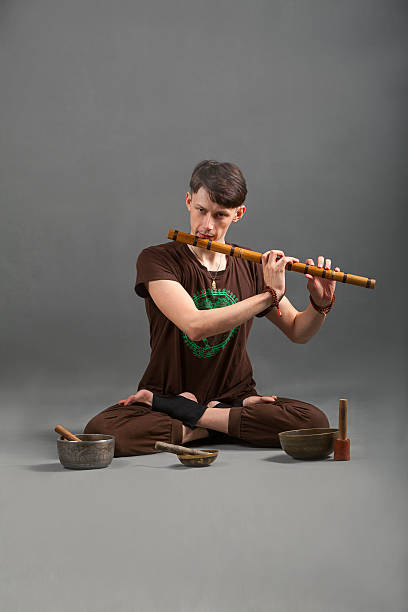 Man playing the flute, singing bowls and tools for meditation. Man playing the flute, singing bowls and tools for meditation. new age music stock pictures, royalty-free photos & images