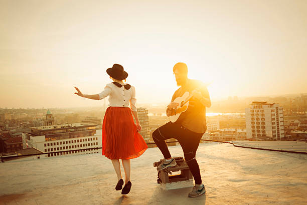 man playing the guitar and the woman dancing stock photo
