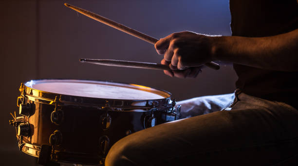 man playing the snare drum on a beautiful colored background man playing the snare drum on a beautiful colored background, the concept of musical instruments drummer stock pictures, royalty-free photos & images