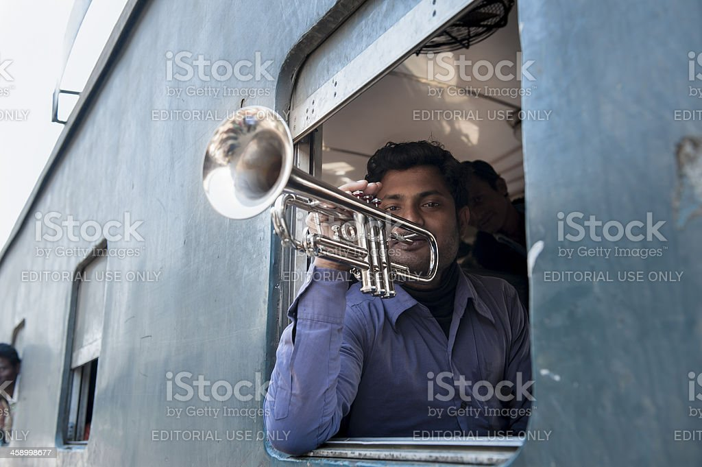 Man playing trumpet at the window of compartment, Bangladesh royalty-free stock photo