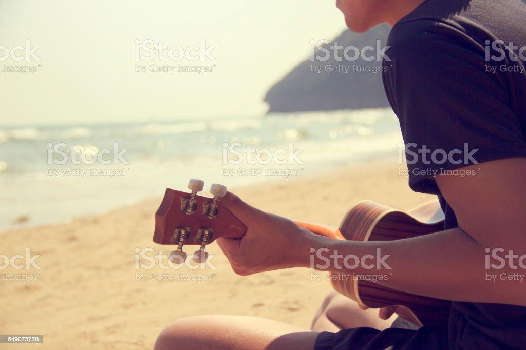 A man playing ukulele on the sandy beach stock photo