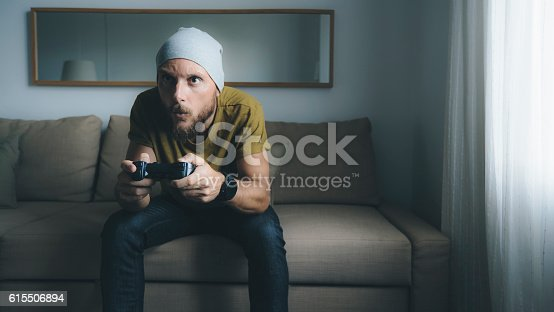Man playing video games at home alone