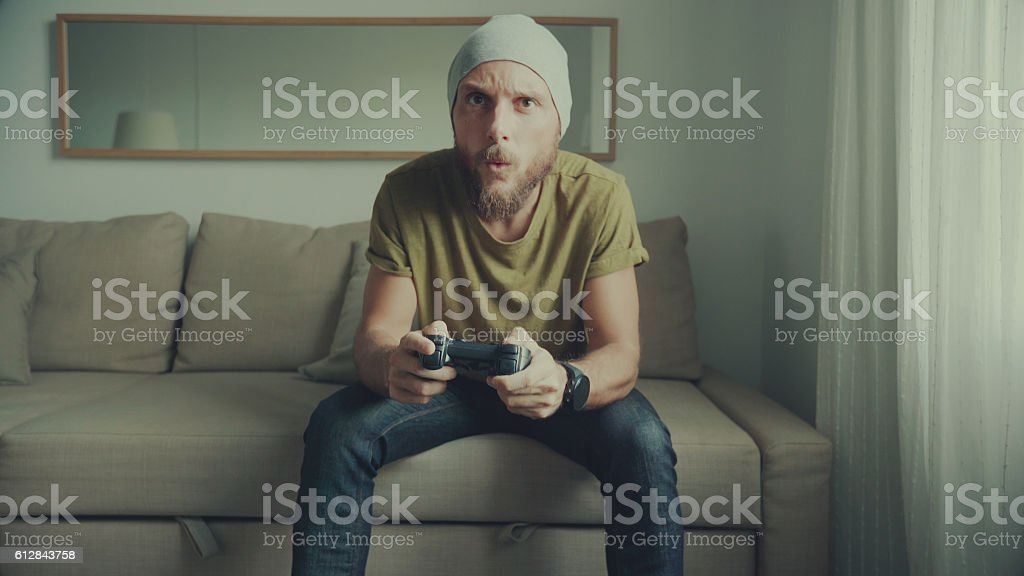 Man playing videogames at home stock photo