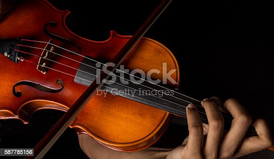 African American Man playing violin holding the bow