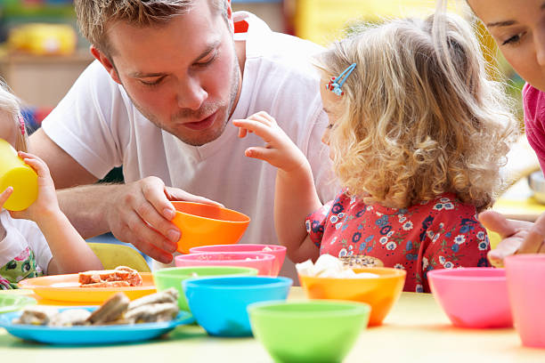 man playing with children using colorful cups - preschool building stock photos and pictures