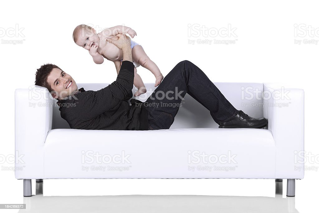 Man playing with his baby on a couch royalty-free stock photo