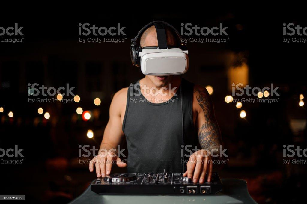 Man plays a DJ mixer with virtual reality glasses. stock photo