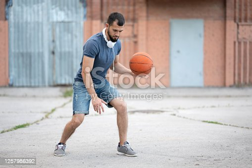 A man plays basketball in the street yard during the day