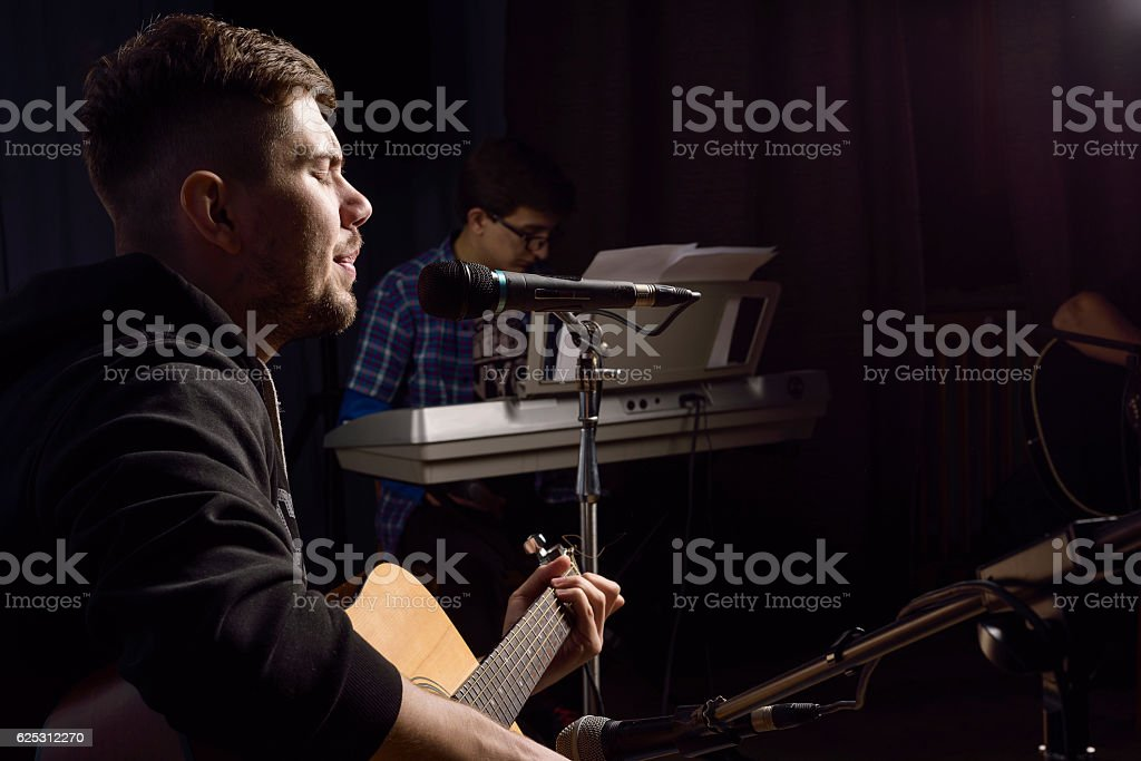 man plays guitar and sings stock photo
