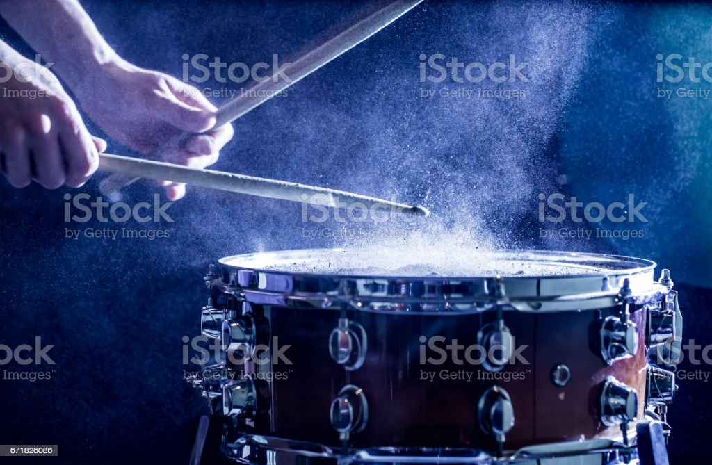 man plays musical percussion instrument with sticks, a musical concept, beautiful lighting on the stage stock photo