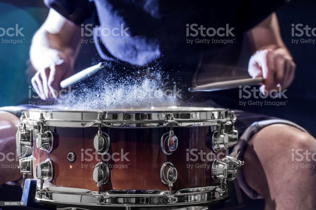 man plays musical percussion instrument with sticks, a musical concept, beautiful lighting on the stage royalty-free stock photo