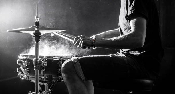 man plays musical percussion instrument with sticks, a musical concept, beautiful lighting on the stage man plays musical percussion instrument with sticks closeup on a black background, a musical concept with the working drum, beautiful lighting on the stage drummer stock pictures, royalty-free photos & images
