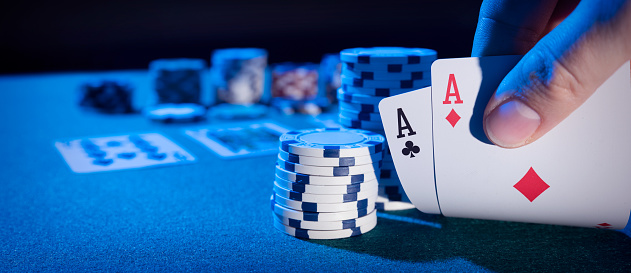 Man plays poker in the casino. Holding cards in hand, gambling concept. Wide image background with copy space.