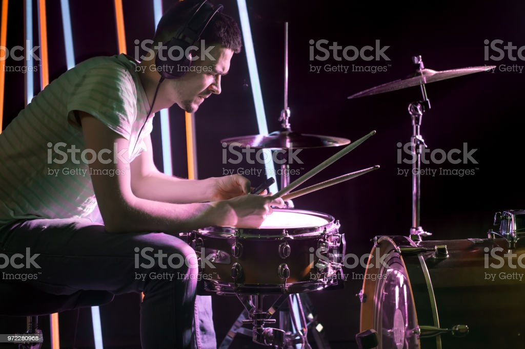 Man plays the drums in the headphones. On the background of colored lights. stock photo