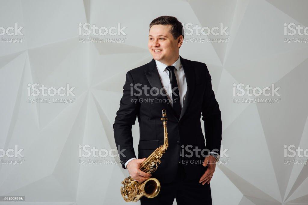 A man plays the saxophone close up stock photo
