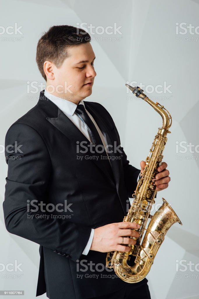 A man plays the saxophone close up stock photo