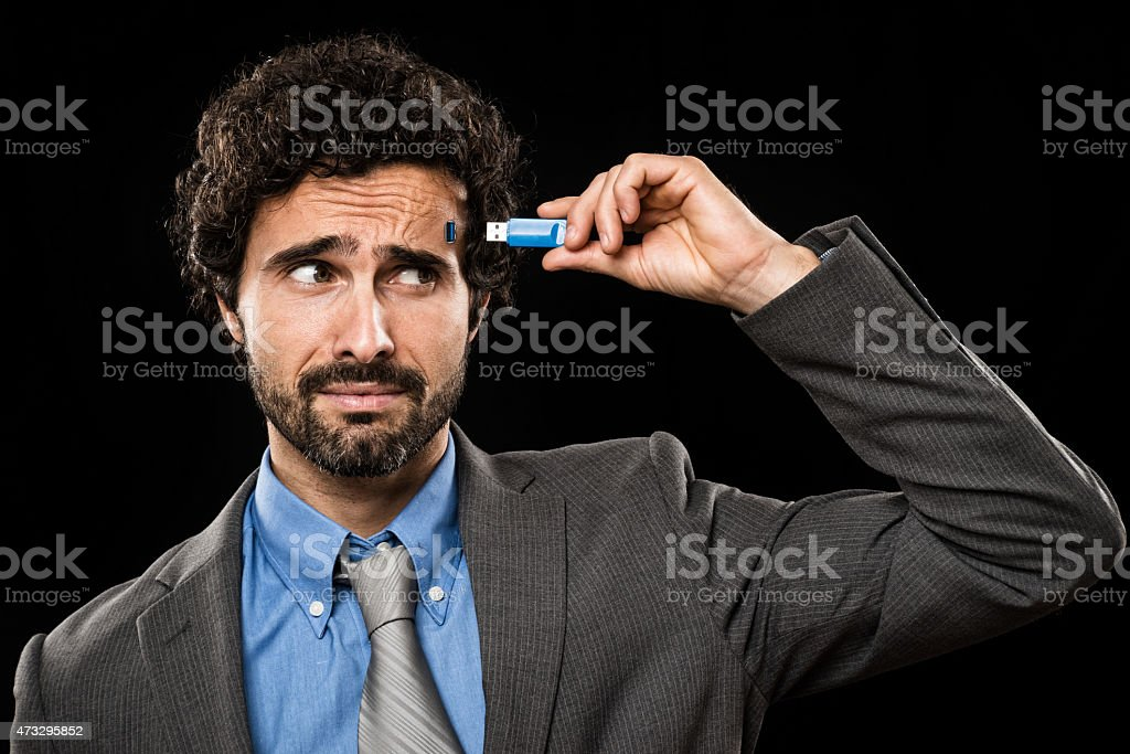 Man plugging a memory stick in his head stock photo